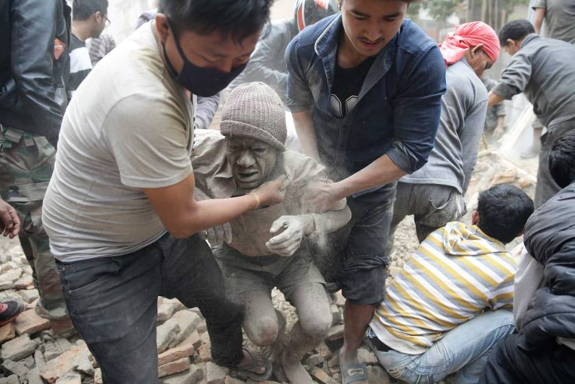 epaselect epa04719889 People free a man from the rubble of a destroyed building after an earthquake hit Nepal, in Kathmandu, Nepal, 25 April 2015. A 7.9-magnitude earthquake rocked Nepal destroying buildings in Kathmandu and surrounding areas, with unconfirmed rumours of casualties. The epicentre was 80 kilometres north-west of Kathmandu, United States Geological Survey. Strong tremors were also felt in large areas of northern and eastern India and Bangladesh. EPA/NARENDRA SHRESTHA
